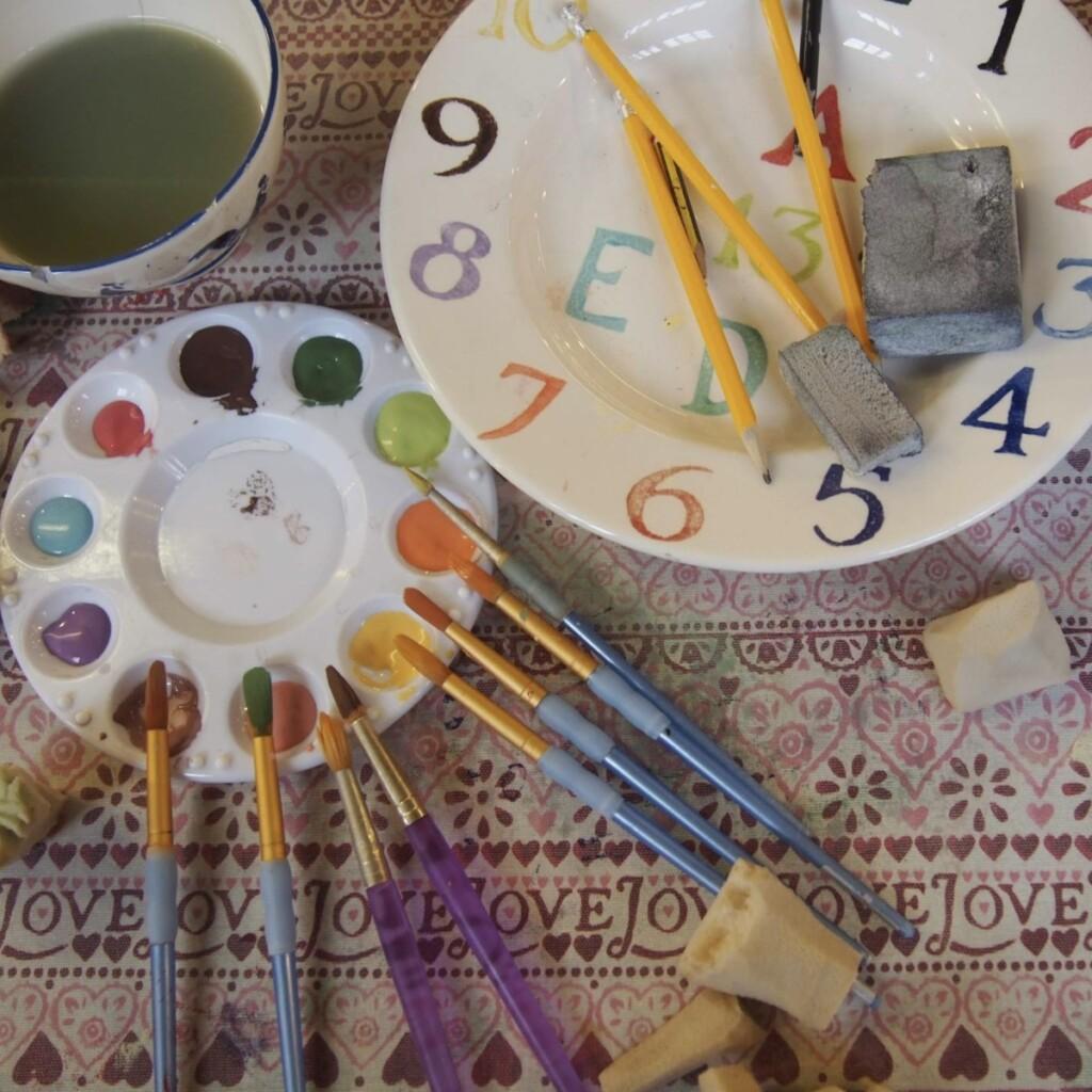 色見本になっているお皿と絵付け用のパレット、絵具と筆