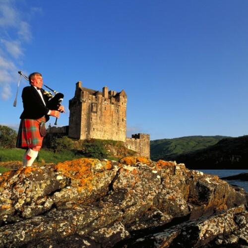 スコットランドのアイリーン・ドナン城をバックにするバグパイプの奏者